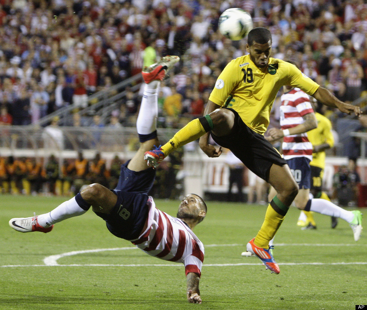 United States' Clint Dempsey, left, shoots past Jamaica's Adrian Mariappa during the first half of a World Cup qualifying soc