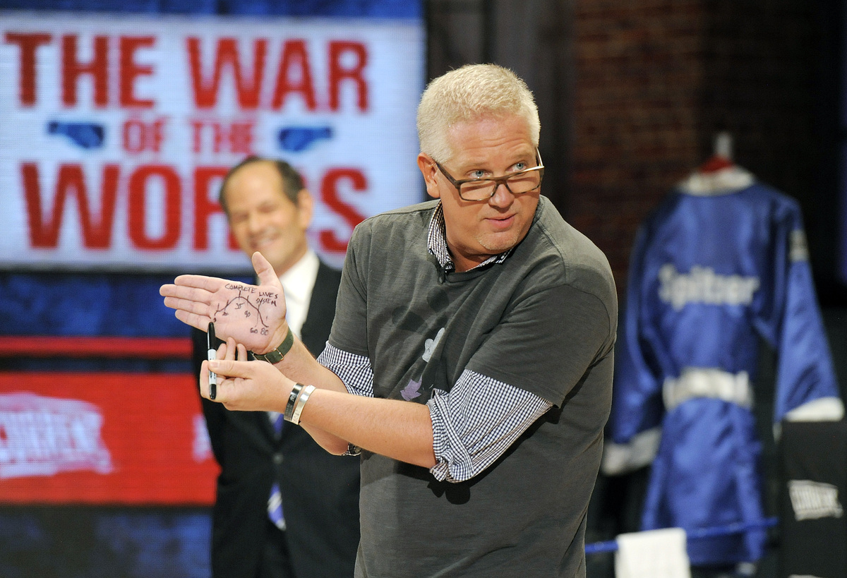 In this photo provided by DISH, Glenn Beck, right, shows a diagram on his hand as he and Gov. Eliot Spitzer, left, square off