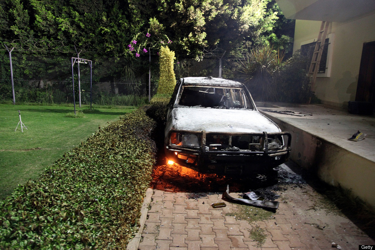 A burnt out vehicle sits smoldering in flames after it was set on fire inside the US consulate compound in Benghazi, late on