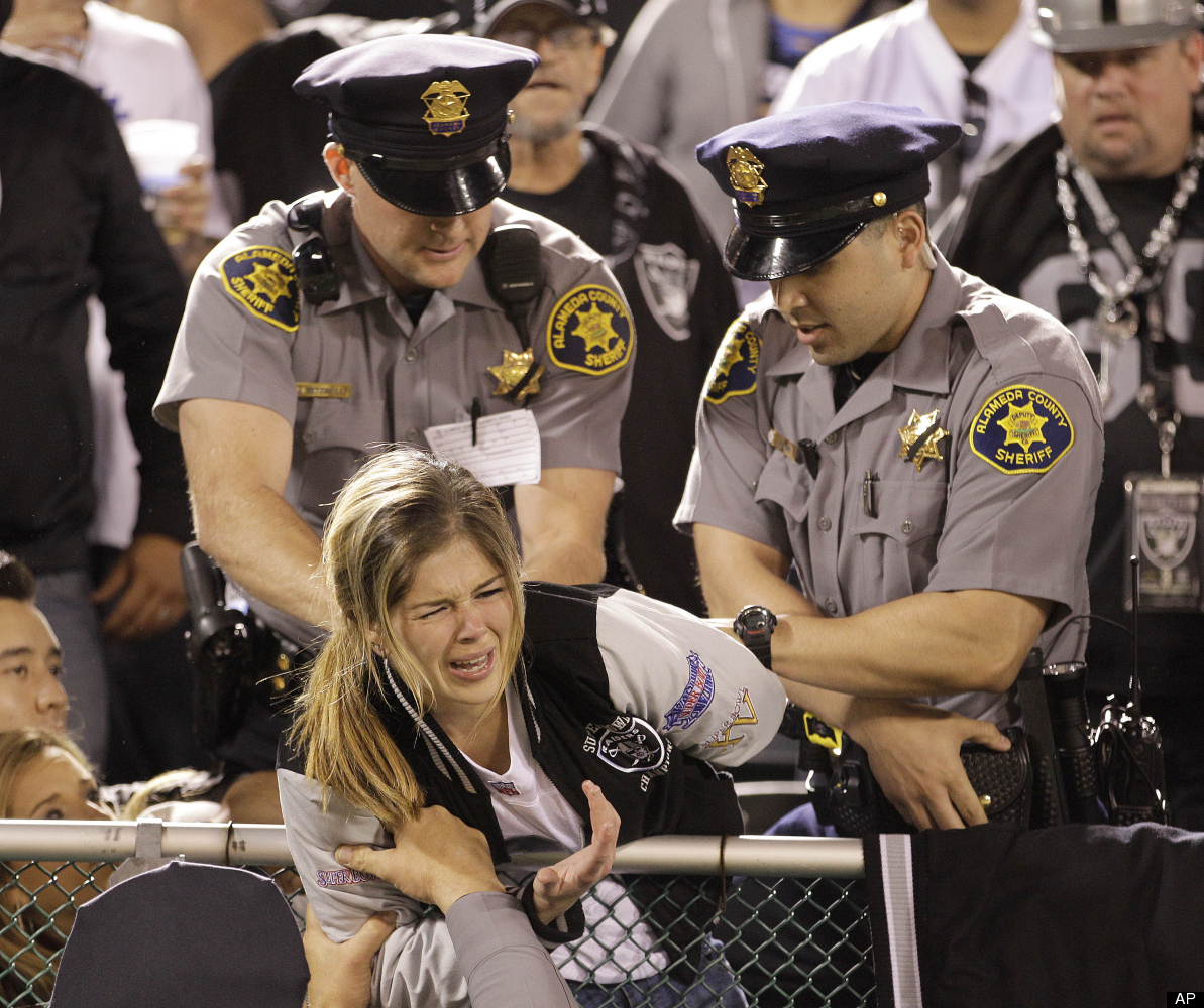 Alameda County Sheriff officers contain a football fan during the second half of an NFL football game between the Oakland Rai