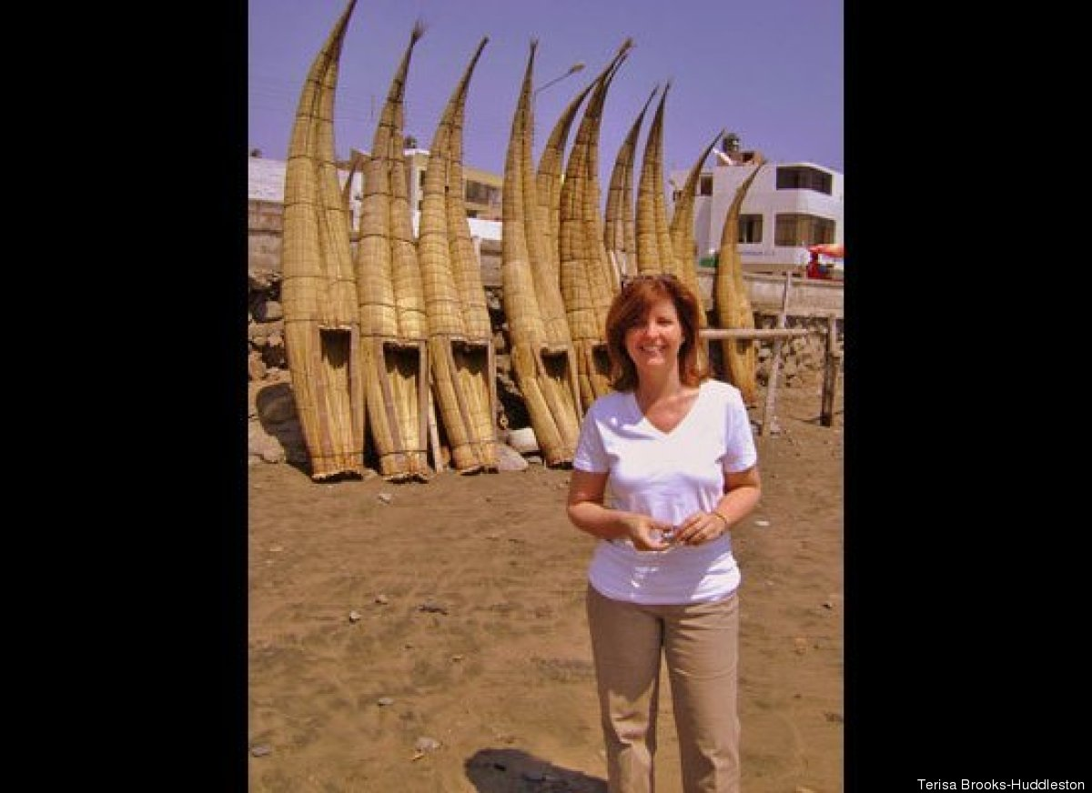 Terisa poses in front of Totora reed fishing boats in Huanchaco, Peru.