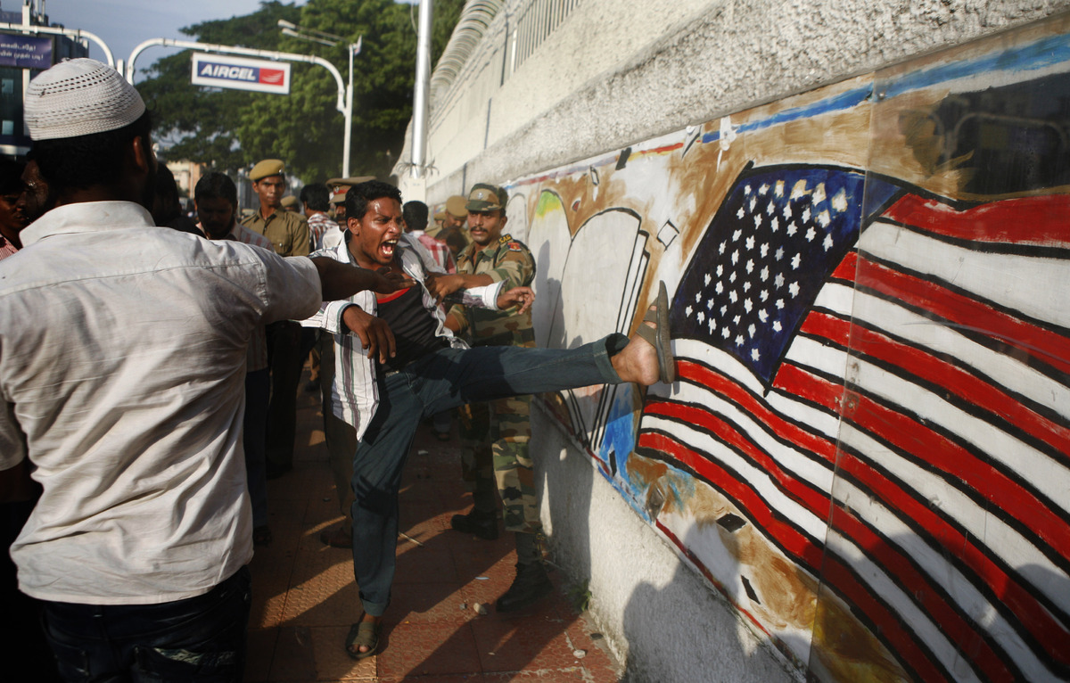 An Indian protester kicks at a graffiti of the American flag on a wall of the U.S. Consulate during a protest against the ant