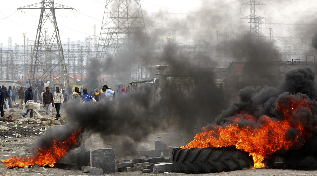 Miners burning tires as they barricade the streets in Lonmin Platinum Mine near Rustenburg, South Africa, Saturday, Sept. 15,