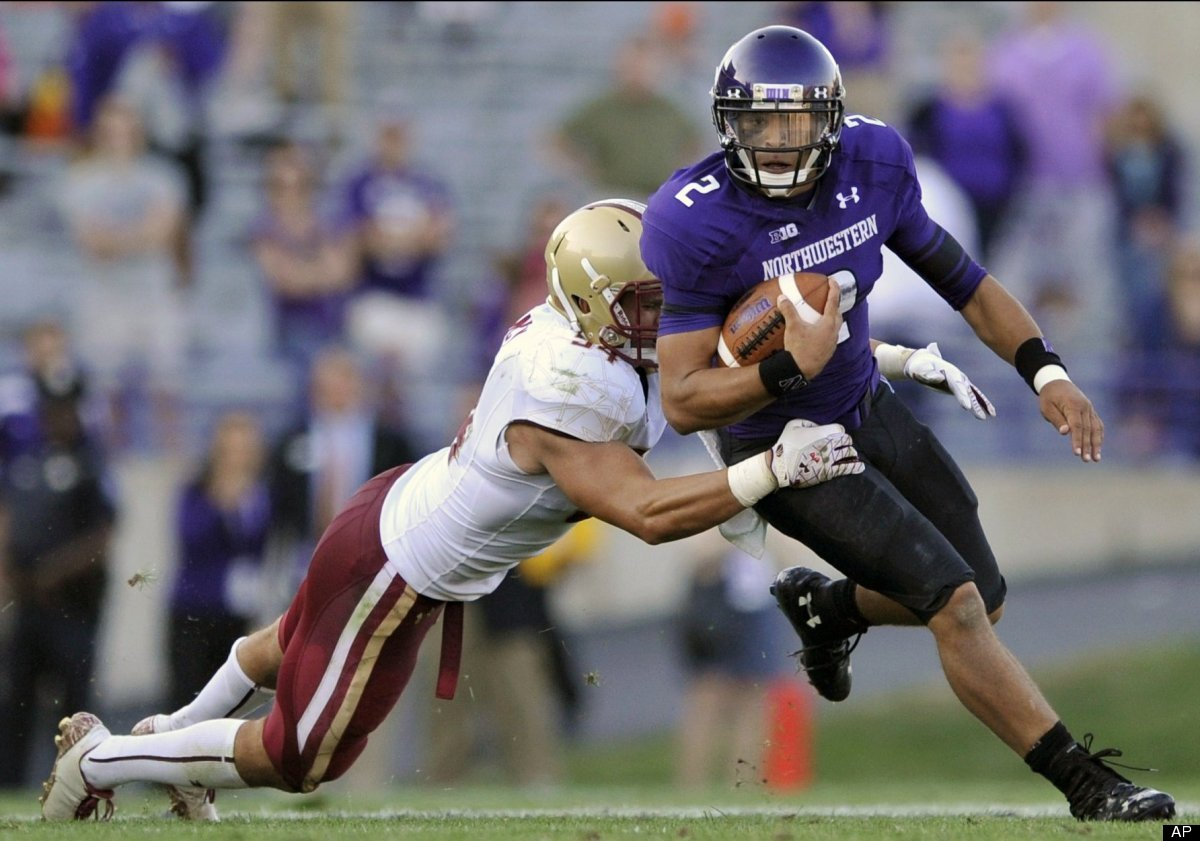 Northwestern quarterback Kain Colter, right, rushes while being tackled by Boston College's Nick Clancy during the fourth qua