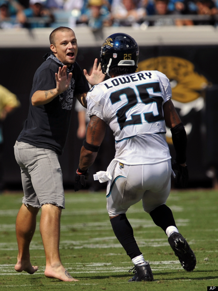 Jacksonville Jaguars strong safety Dwight Lowery (25) grabs a fan that ran onto the field during the second half of an NFL fo