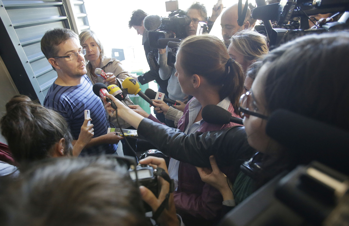 Publishing director of the satyric weekly Charlie Hebdo, Charb, holds the newspaper as he talks to the media in Paris, on Wed
