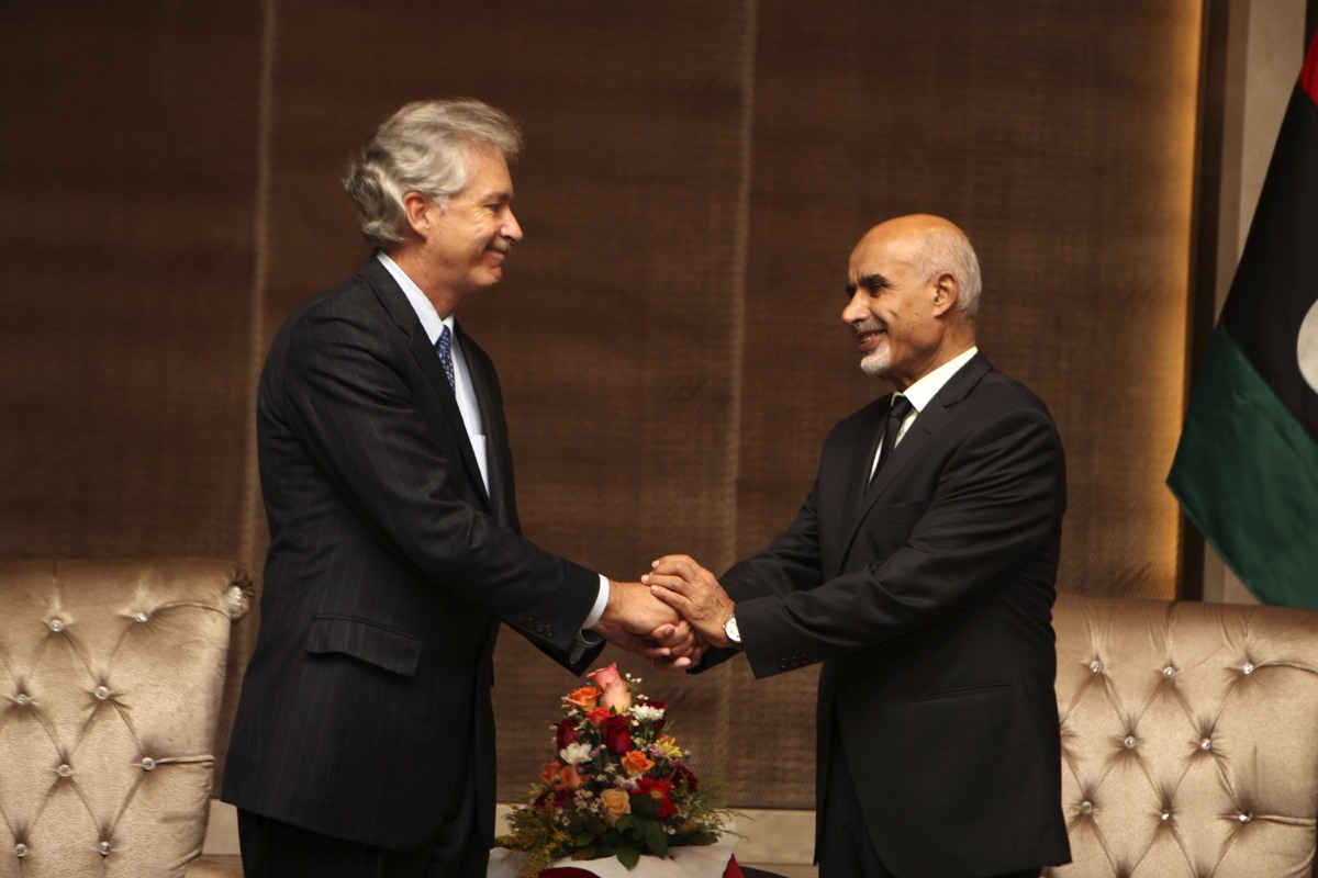 U.S. deputy Secretary of State William Burns, left, shakes hands with Libyan President Mohammed el-Megarif during a memorial