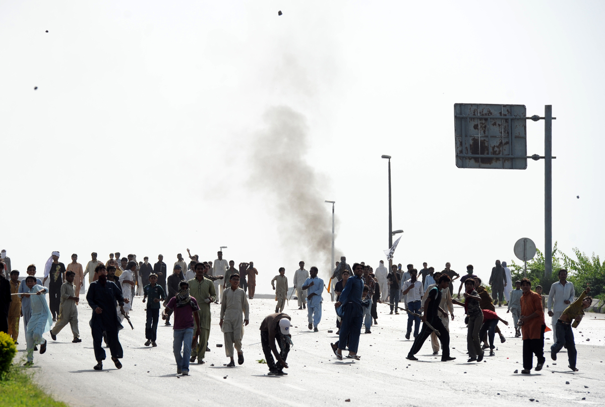 Pakistani demonstrators throw stones toward riot police during a protest against an anti-Islam film in Islamabad, on Septembe