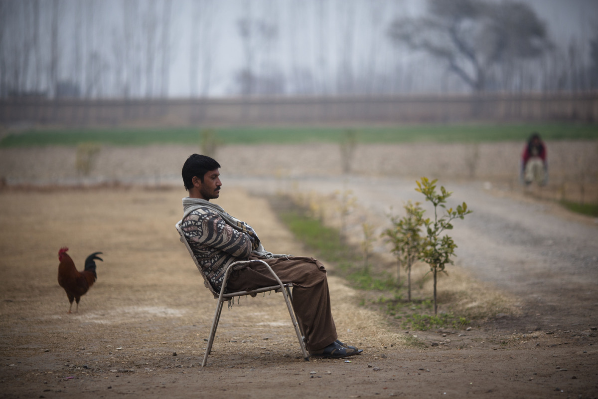 In this Sunday, Feb. 12, 2012, photo, a Pakistani drug addict sits on a chair guarding the premises at the Dost Foundation in