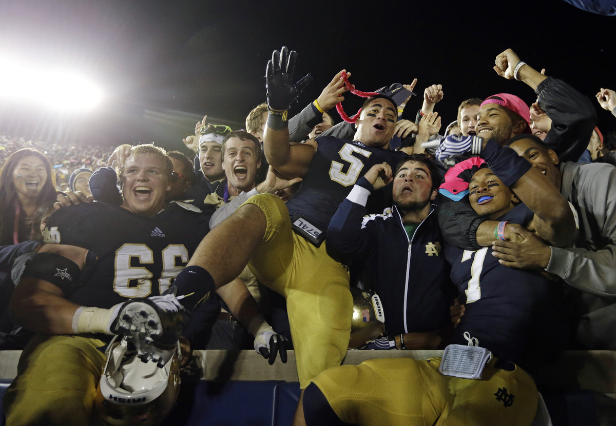 Notre Dame's Chris Watt (66), Manti Te'o (5) and TJ Jones (7) celebrate with fans after Notre Dame defeated Michigan, 13-6, i