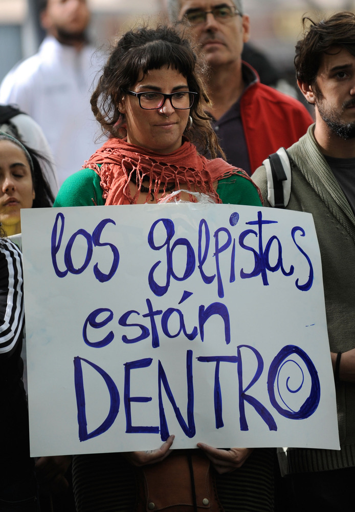 A protestor holds a sign which reads, 'The Coup d'Etat is inside [parliament],' before a demonstration surrounding the Spanis