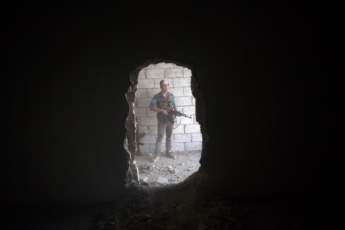 Free Syrian Army fighter takes cover in a building during clashes against the Syrian Army in Aleppo, Syria, Tuesday, Sept. 25