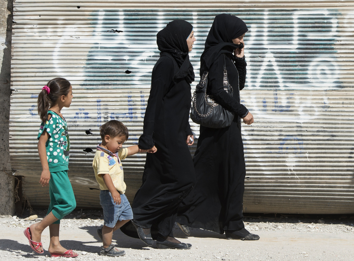 Syrians walk past a closed shop in the northern town of Azaz, on the border with Turkey, on September 29, 2012. More than 30,
