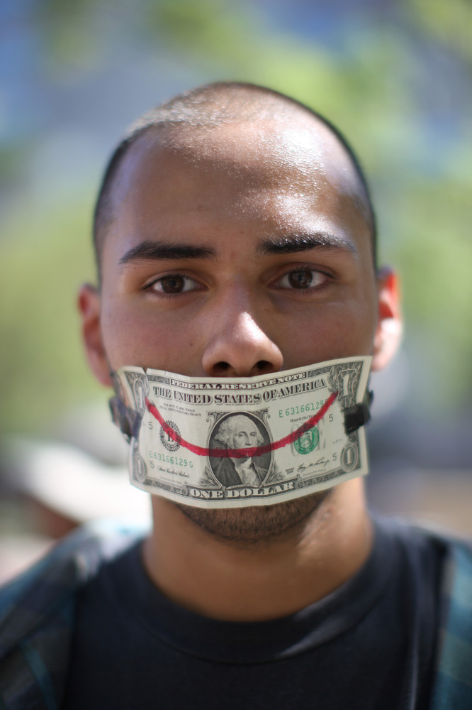 LOS ANGELES, CA - OCTOBER 1:  Alex Chavaria wears a dollar bill over his mouth as protesters rally in the downtown financial
