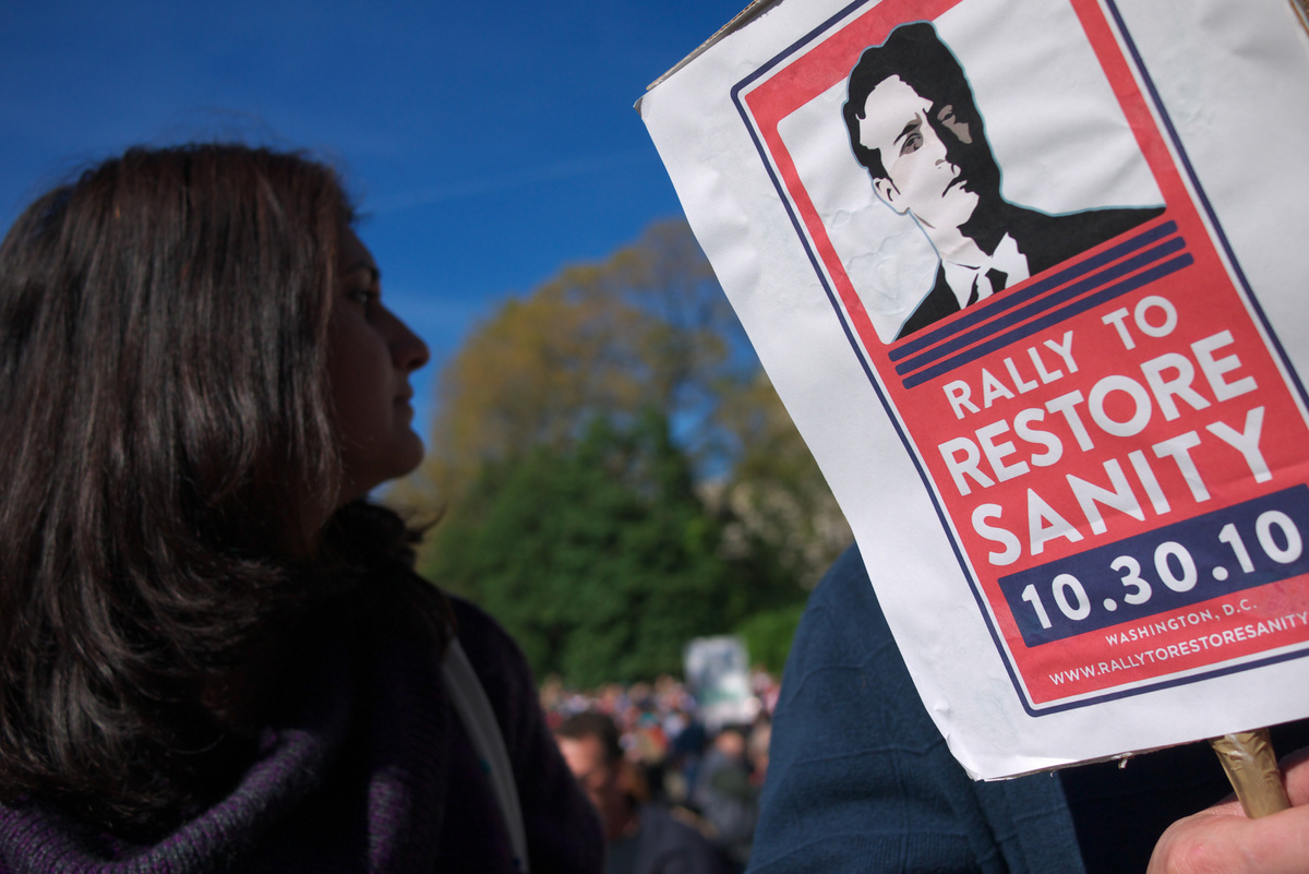 A woman stands next to a placard for Jon Stewart as people gather on the Mall to attend the Rally to Restore Sanity and/or Fe