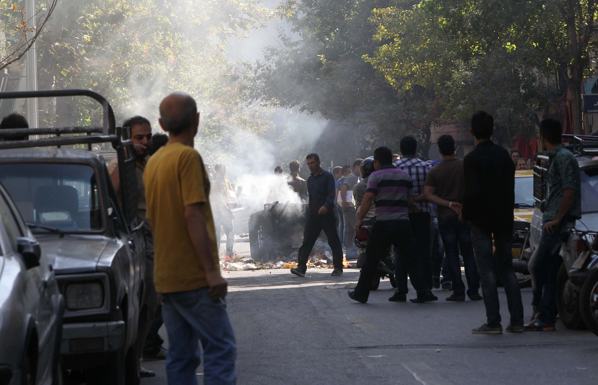 Iranian protesters gather next to a garbage container which is set on fire during scuffles with police in central Tehran, nea