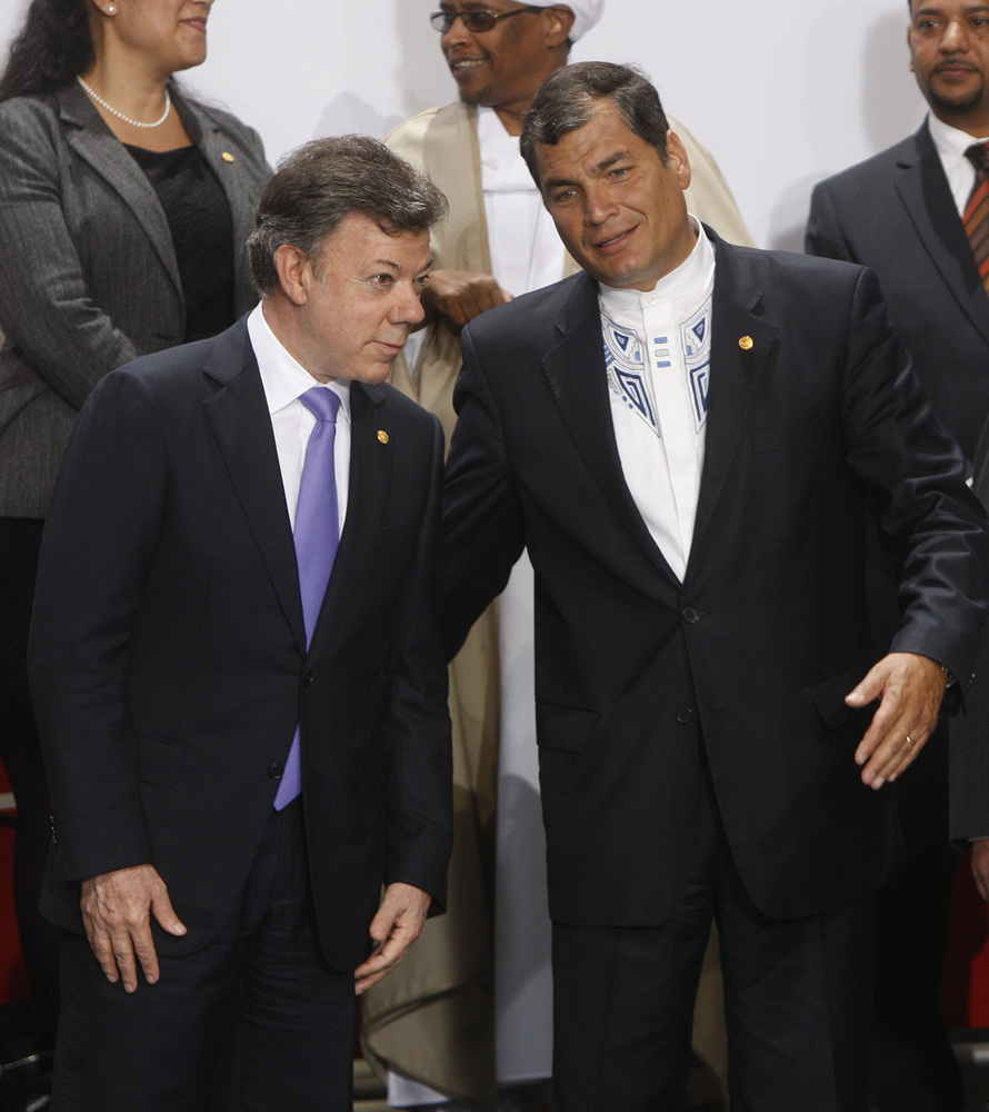Ecuador's President Rafael Correa, right, speaks to Colombia's President Juan Manuel Santos, left, as they form for the takin