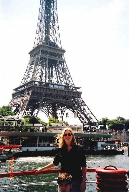 A body-less demon child decided to jump into Amy Gibson's keepsake shot of her in front of the Eiffel Tower in 2002. Looks li