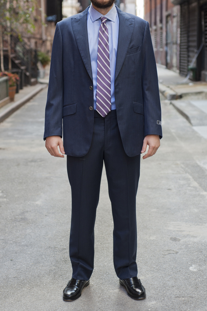 The average American guy is wearing a suit that is one or two sizes too big. Larger clothes do not make you look more muscula