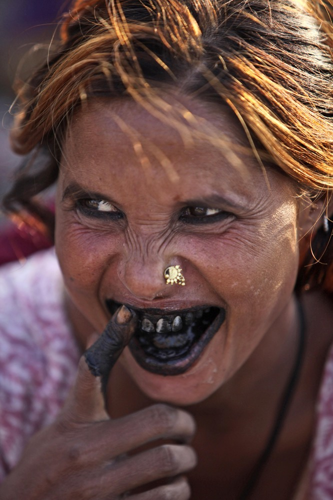 An Indian woman cleans her teeth with coal at a slum area in Jammu, India, Thursday, Oct. 4, 2012. (AP Photo/Channi Anand)