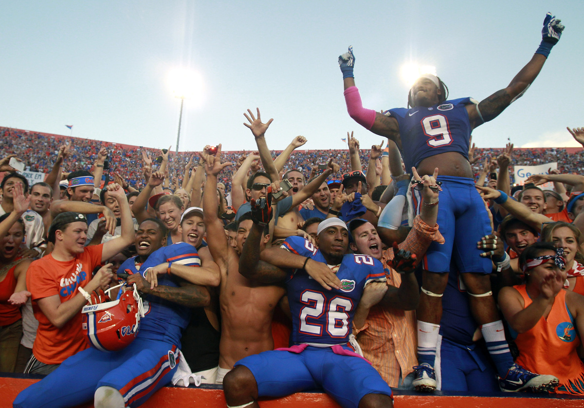 Florida defensive backs Marcus Roberson, left, De'Ante Saunders (26) and Josh Evans (9) celebrate with fans after defeating L