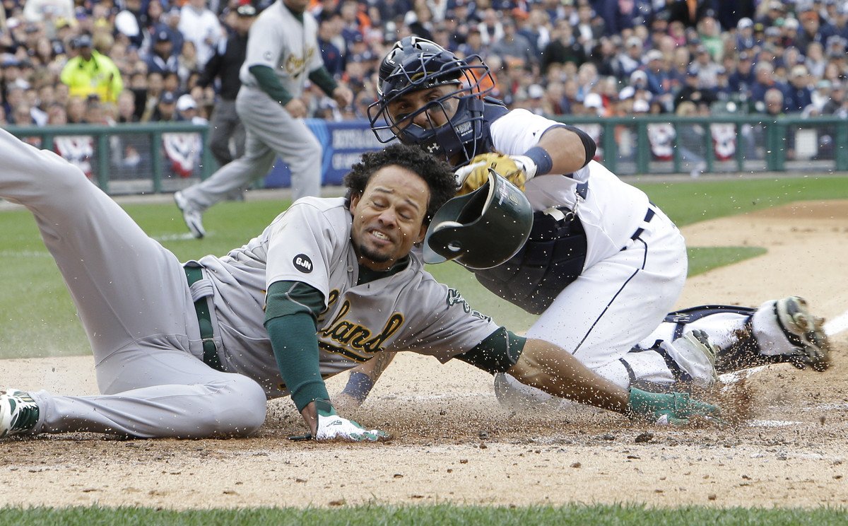 Oakland Athletics' Coco Crisp is tagged out by Detroit Tigers catcher Gerald Laird (9) trying to score from second on teammat