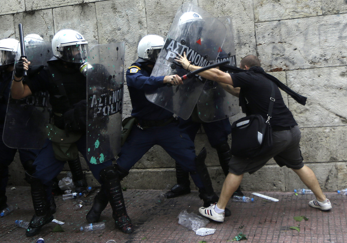 A protester clashes with police during a protest in front of the parliament in Athens, Tuesday, Oct. 9, 2012. Paying her firs