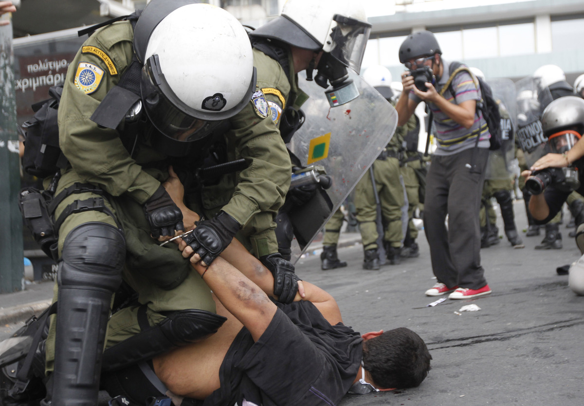 Riot police arrest a demonstrator during clashes in front of the parliament in Athens, Tuesday, Oct. 9, 2012.  (AP Photo/Niko