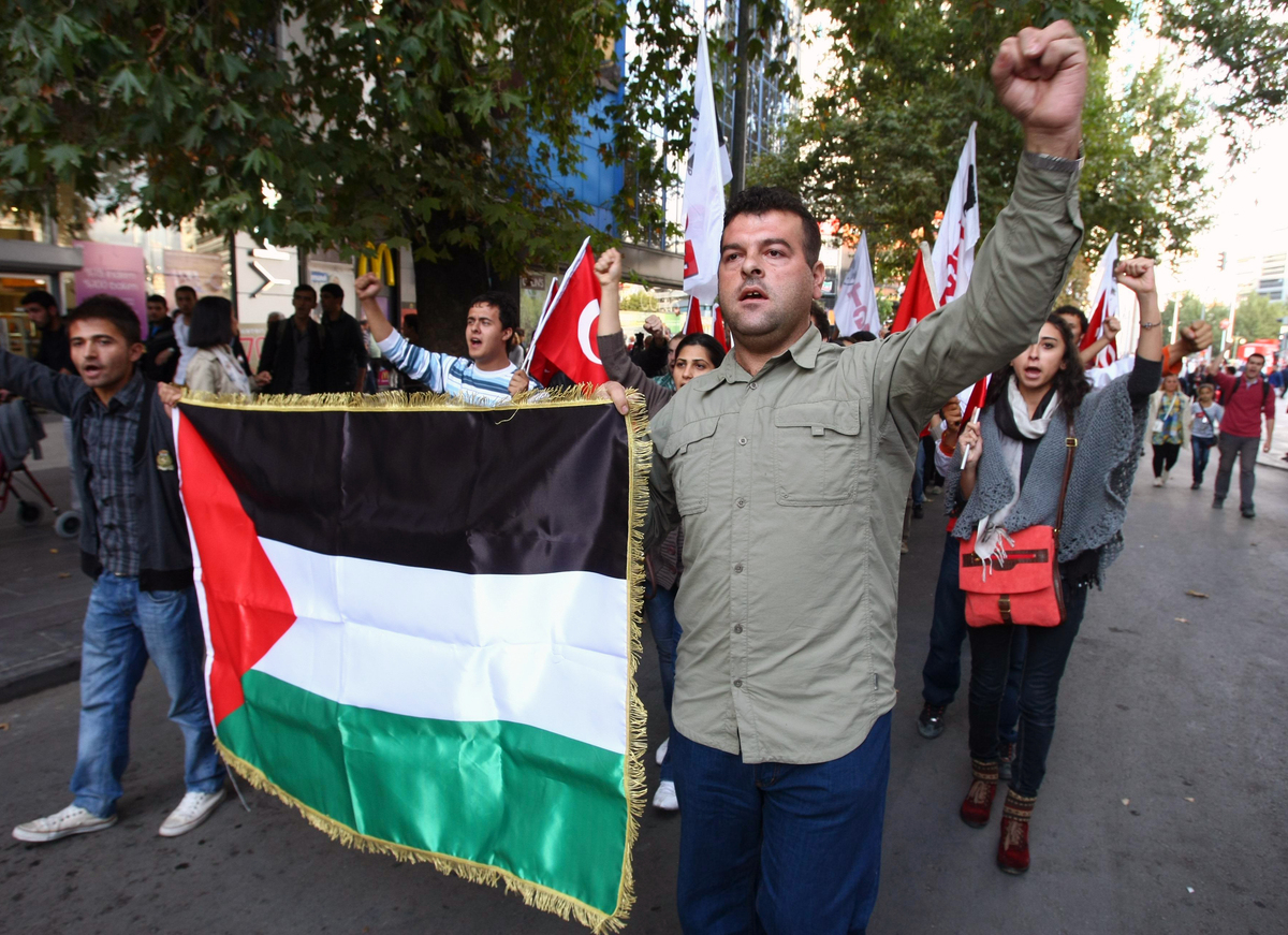 Members of the Union of Turkish Youth hold Turkish, Syrian and Palestinian flags as they march during an anti-war protest and