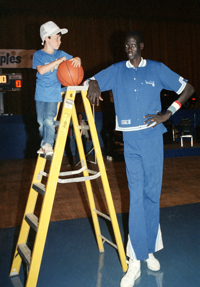 "Manute Bol 7'9"" basketball player poses with 6-year-old Darren Moss, the son of the owner of the Rhode Island Gulls in 1985."