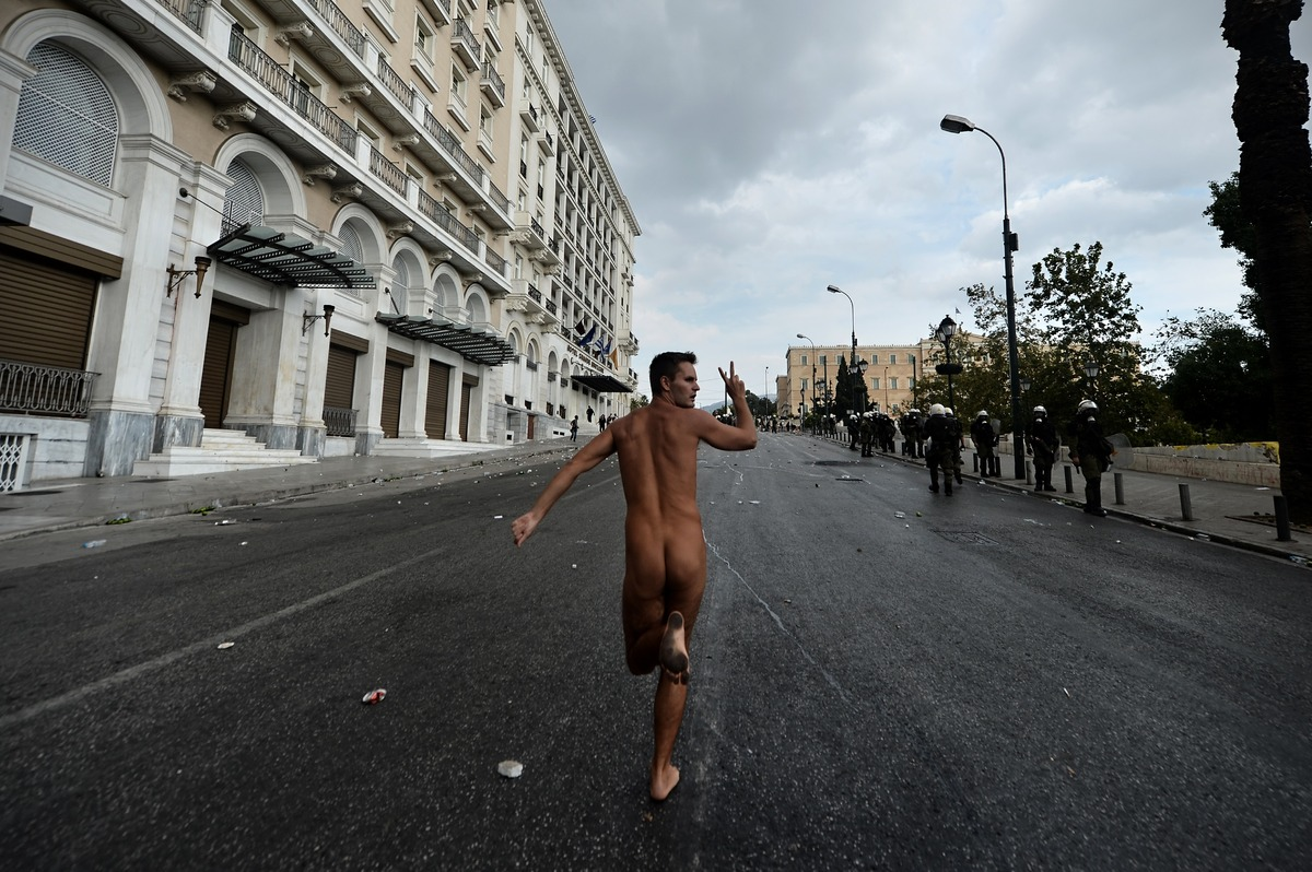 A naked demonstrator flashes the victory sign while running in Athens during a demonstration against the vist of the German C