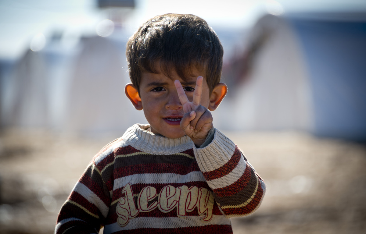 Standing in front of a row of plastic tents a young boy flashes the V-sign in a refugee camp on the border between Syria and
