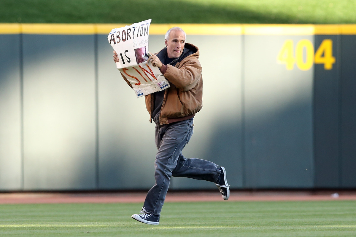 A man runs onto the field holding a sign saying 'Abortion is Sin' before the Cincinnati Reds take on the San Francisco Giants