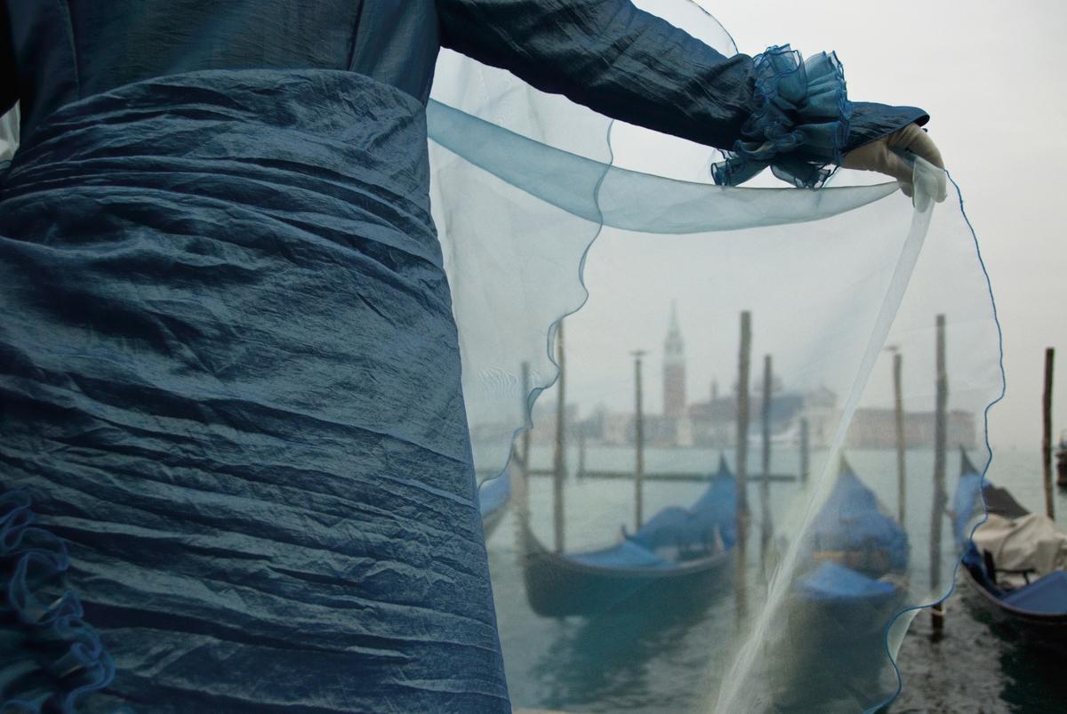 Venice, Italy  A tourist unfurls a gauzy blue veil near San Marco Basin.