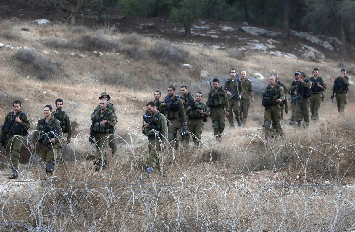Israeli soldiers are seen after searching for the remains of a drone in the Negev southern Israel, Saturday, Oct. 6, 2012. (A
