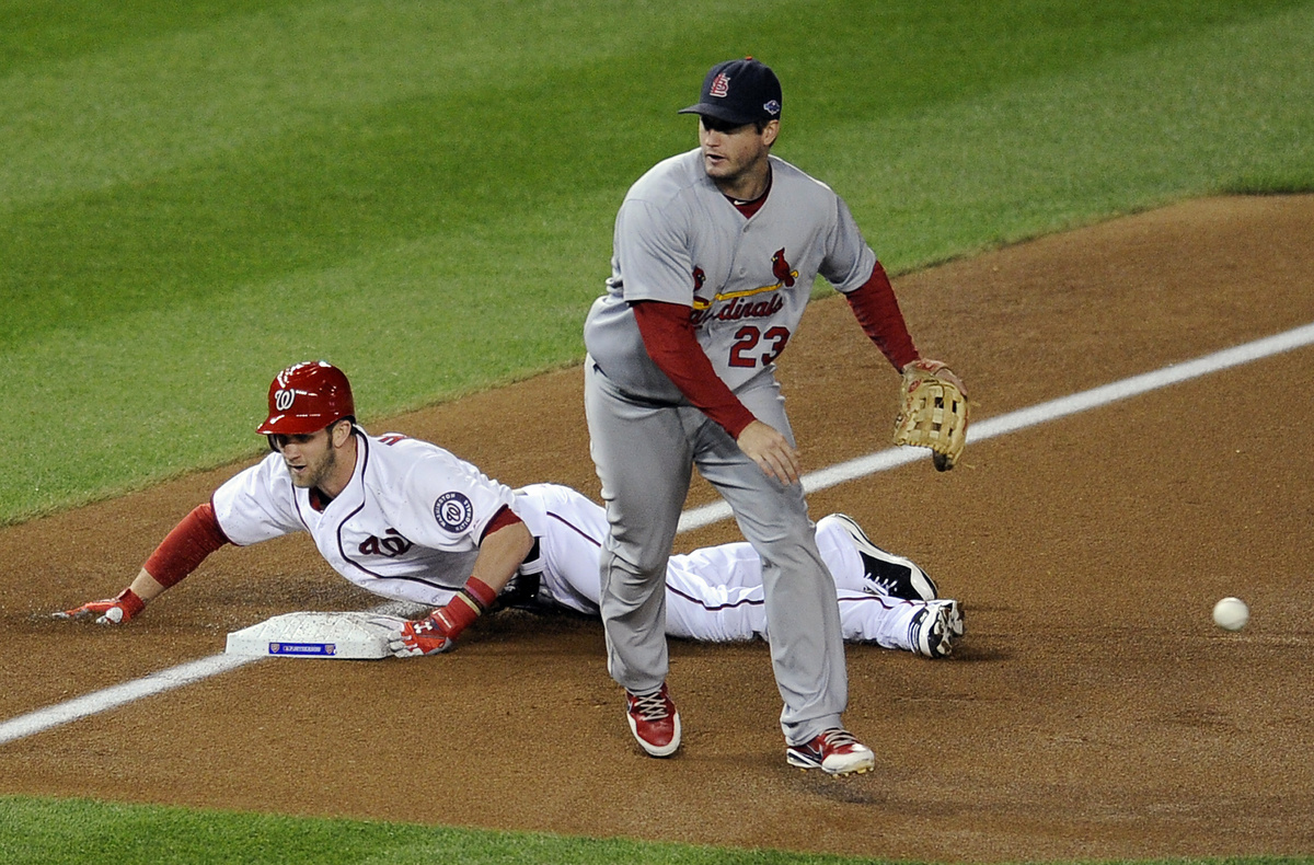 Washington Nationals' Bryce Harper, back, slides into third base for a triple as the throw goes wide of St. Louis Cardinals t