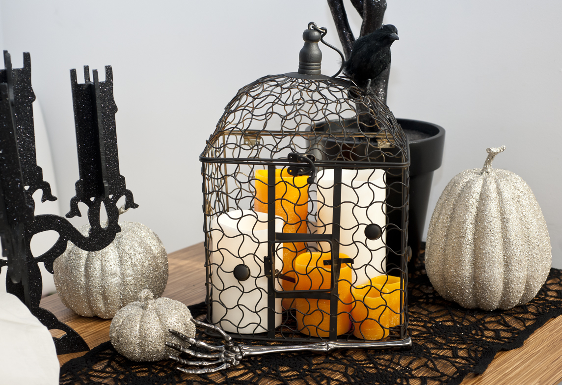 We grouped several candles of various sizes inside a birdcage as a flickering centerpiece that illuminates our tablescape.