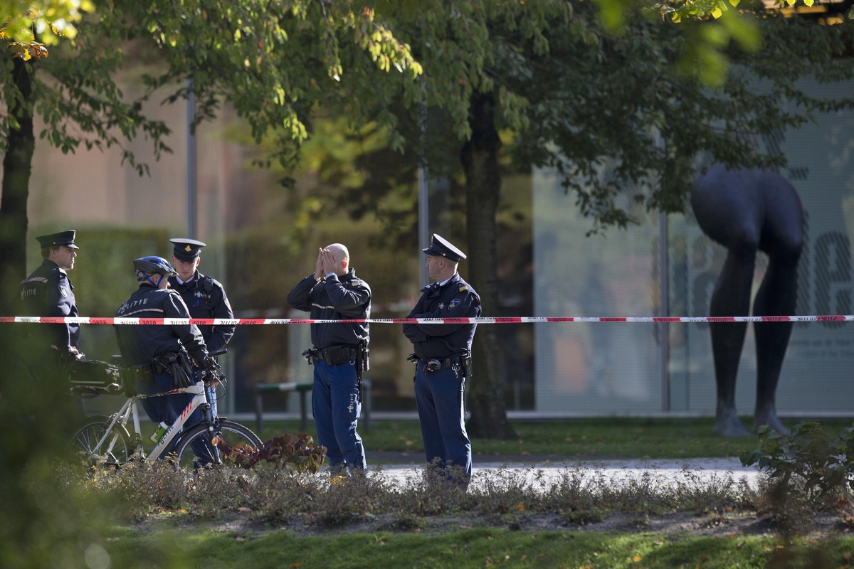 Police officers guard a cordoned off area at the rear side of the Kunsthal museum in Rotterdam, Tuesday Oct. 16, 2012. Severa