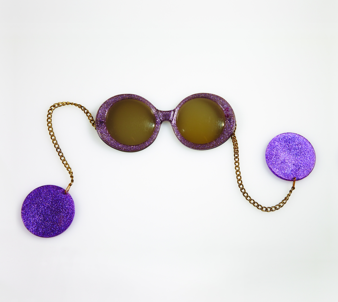 A modern take on a centuries-old form of eyewear, these 1960s sunglasses feature chains that loop around the ears and are wei