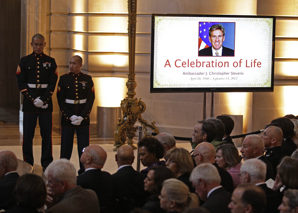 A Marine honor guard stands beside people attend a public memorial in honor of slain U.S. Ambassador J. Christopher Stevens i