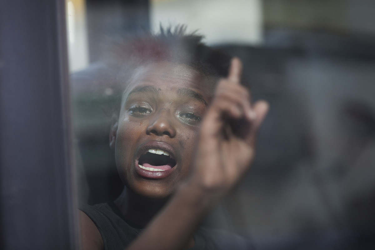 A young suspected crack user reacts as she sits inside a van waiting to be taken to a shelter after being removed from the st