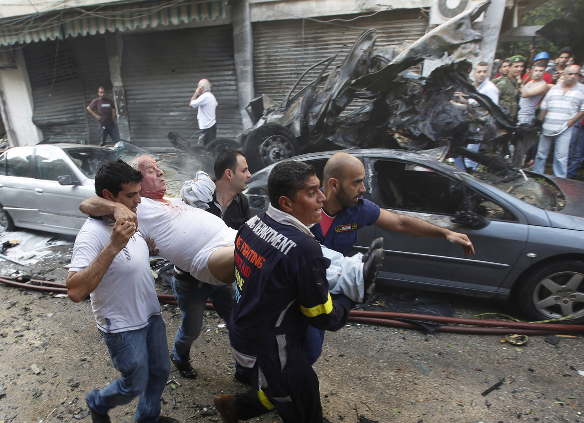 Lebanese rescue workers and civilians carry an injured man, from the scene of an explosion in the mostly Christian neighborho