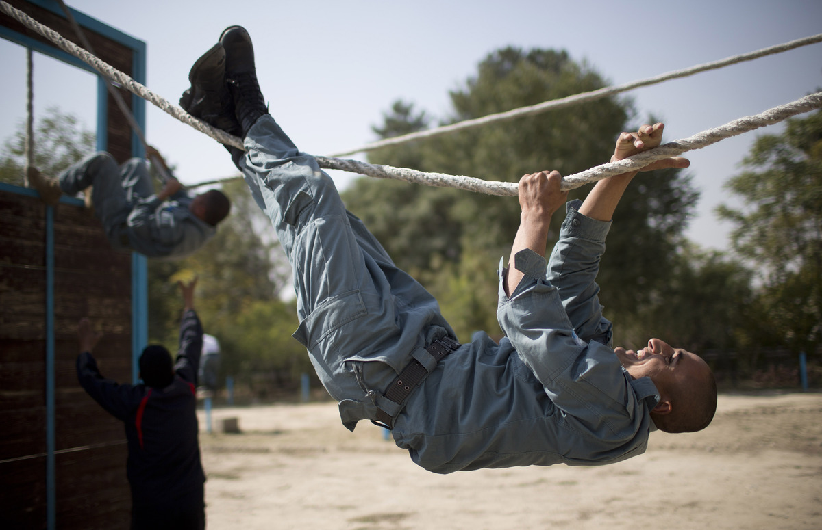In this Saturday, Oct. 13, 2012 photo, Afghan National Police officers navigate a ropes course during a training session at t