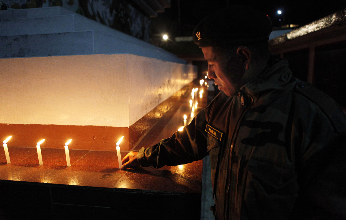 An Indian army soldier places a candle as he pays homage to the martyrs of the 1962 India-China war at the war memorial in Ta