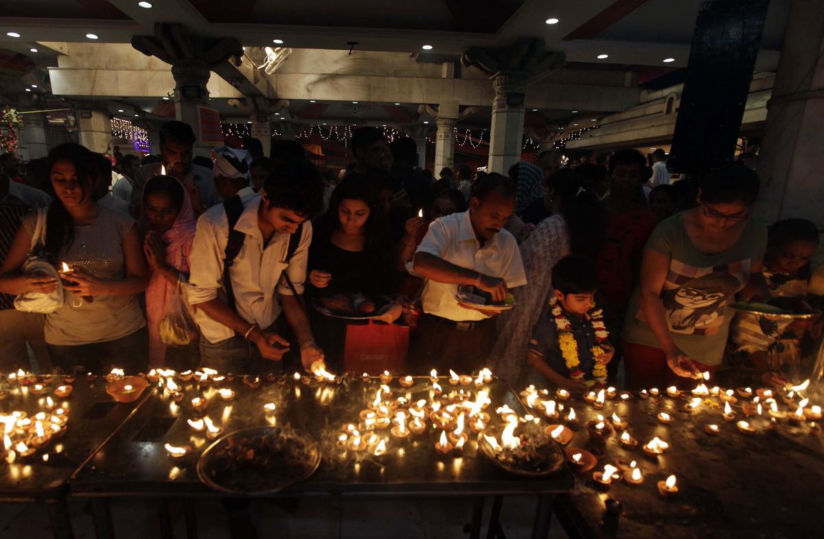 Hindu devotees light oil lamps at a temple on the first day of Navratri or the festival of nine nights in New Delhi, India, T