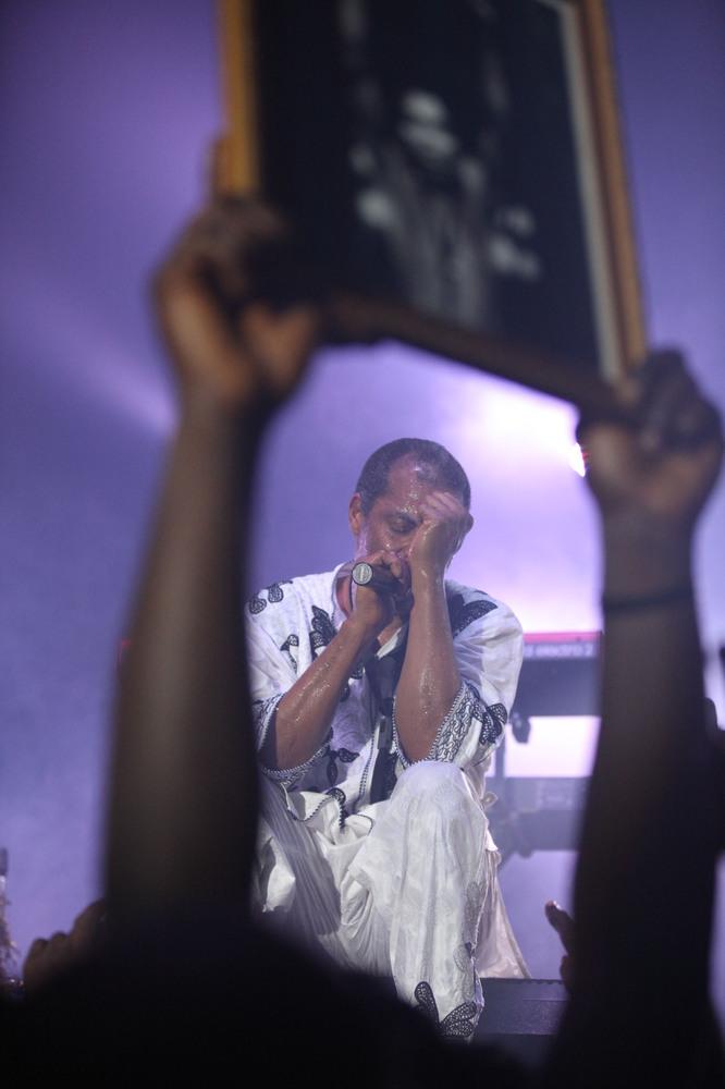 Femi Kuti, son of Afrobeat legend Fela Anikulapo-Kuti, performs as a Fan hold a portrait of late Fela Kuti at the New Afrika