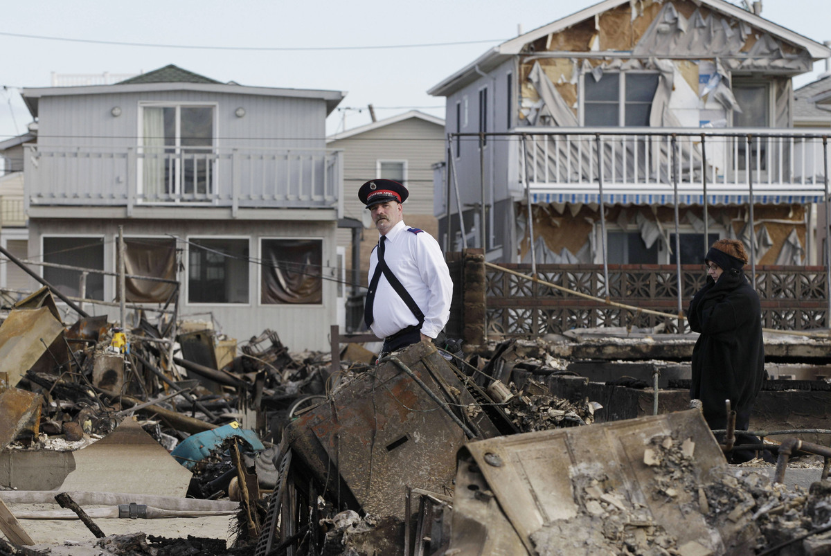 A representative of the Salvation Army walks past homes destroyed by Superstorm Sandy in Breezy Point, Sunday, Nov. 4, 2012,