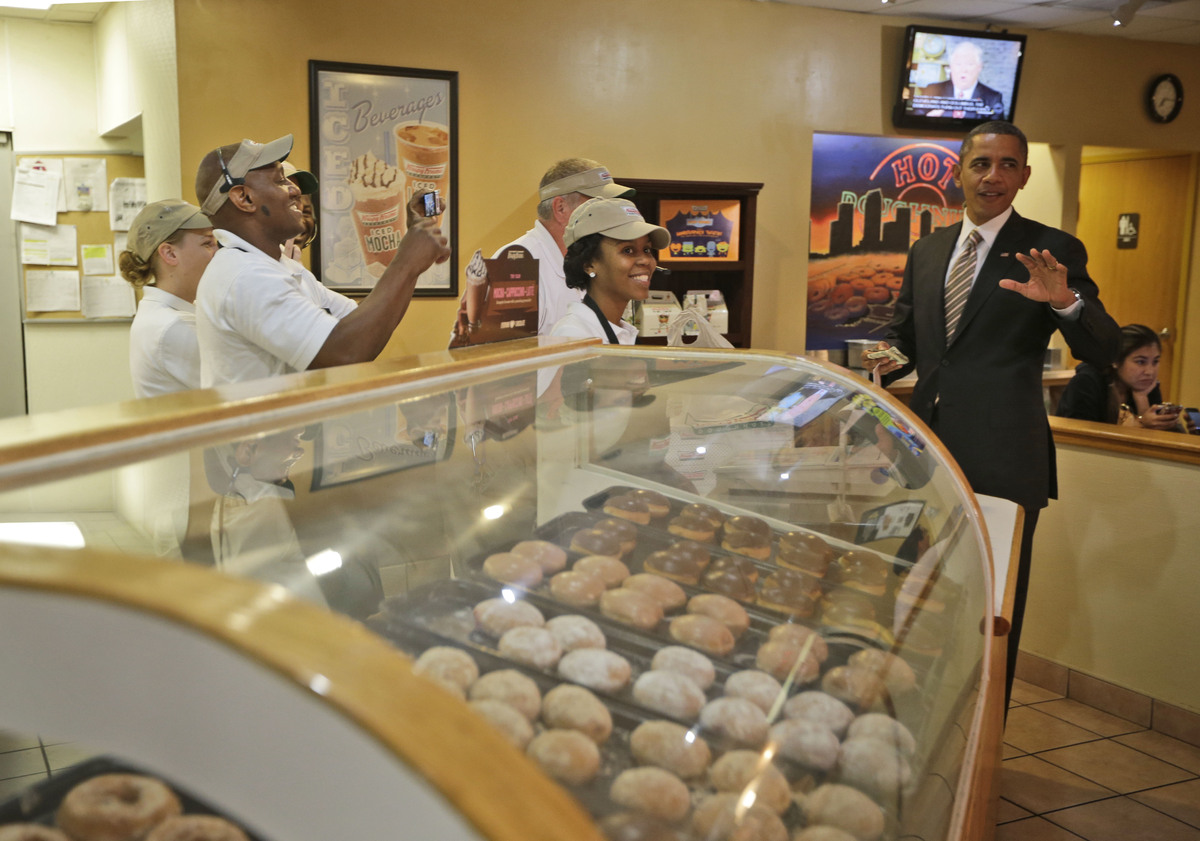 President Barack Obama pays for his order during an unannounced visit to Krispy Kreme Doughnuts, Thursday, Oct. 25, 2012, in