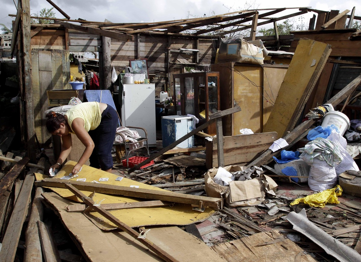 Resident Barbara Garces tries to recover her belongings from his house destroyed by Hurricane Sandy in Aguacate, Cuba, Thursd