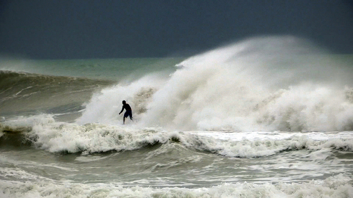 A surfer rides some of the rare waves driven by Hurricane Sandy at South Beach in Miami Friday, Oct. 26, 2012. Hurricane Sand
